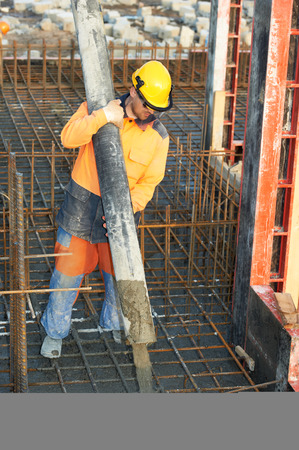 concrete pump: builder worker with boom pump pouring concrete on metal rods reinforcement of formwork