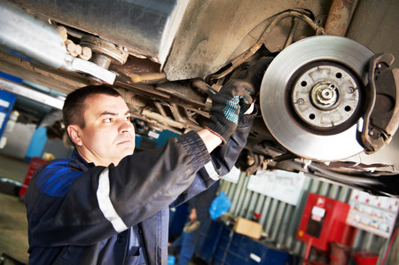 automobile mechanic inspecting car wheel brake disc and shoes of lifted automobile at repair service station