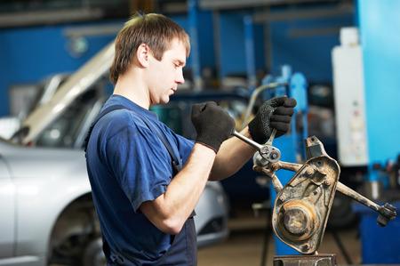 palanca: trabajador mecánico automotriz apriete el tornillo con la llave inglesa durante el mantenimiento de automóvil en la palanca de la estación de servicio de reparación