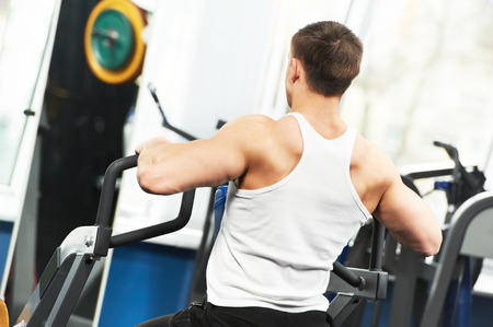 weight machine: athlete bodybuilder man doing back muscles exercises at weight machine in fitness sport club gym