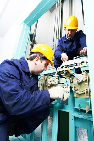 two male technician machinist worker at work adjusting elevator mechanism of lift with spanner Stock Photo