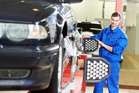 vision repair: car mechanic installing sensor during suspension adjustment and automobile wheel alignment work at repair service station
