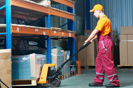 unloading: male worker in warehouse working with hand forklift