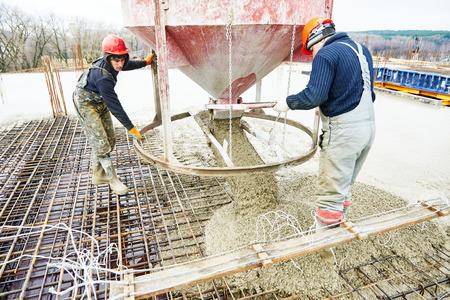 コンクリート作業: スキップと建坪で型枠にコンクリートを注ぐことの間に建設現場労働者