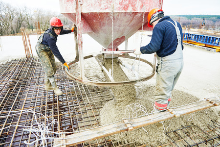 formwork: concreting work: construction site worker during concrete pouring into formwork at building area with skip