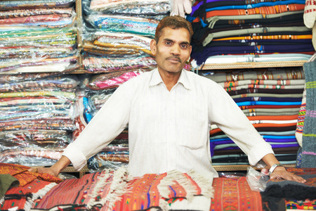 small shop owner indian man selling shawls, clothing and souvenirs at his store Stock Photo