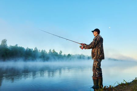 Fisher man fishing with spinning rod on a river bank at misty foggy sunrise photo