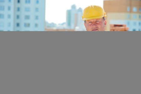sand lime bricks: construction worker. Portrait of mason bricklayer installing red brick with trowel putty knife outdoors Stock Photo