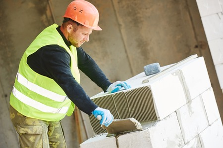 sand lime bricks: Bricklaying work. construction worker mason bricklayer installing calcium silicate brick