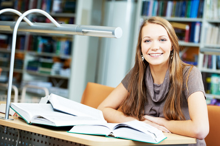 library student: Studying young teenage college student girl  in a library with books