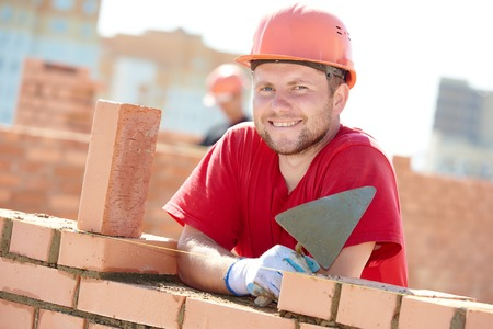 construction worker. Portrait of mason bricklayer installing red brick with trowel putty knife outdoors 스톡 콘텐츠