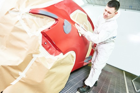 auto mechanic worker wiping car body at automobile repair and renew service station shop in painting chumber photo