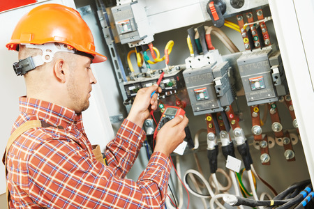 electrical contractor: adult electrician builder engineer worker with electric scheme plan in front of fuse switch board