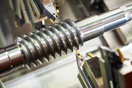 metales: industria metalmecánica. herramienta de corte de piñón espiral de metal de acero de procesamiento o el eje de tornillo sin fin en la máquina del torno en el taller. Centrarse en la herramienta.