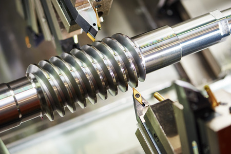 metalworking  industry. cutting tool processing steel metal spiral pinion or worm screw shaft on lathe machine in workshop. Focus on tool.