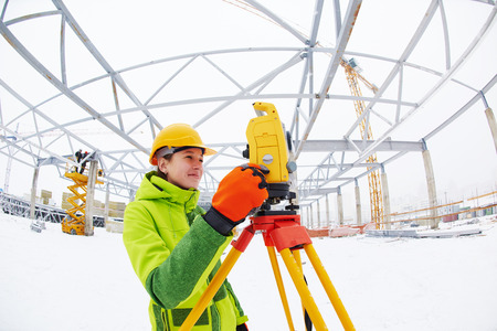 tachymeter: female surveyor worker working with theodolite transit equipment at road construction site outdoors
