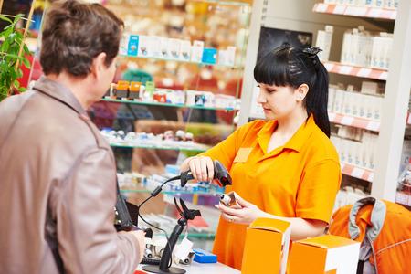 女性販売レジのバーコード スキャナーを使用してハードウェア ショッピング モールのスーパー マーケットでの購入者にランプを販売中