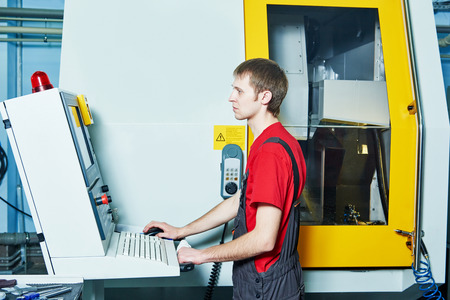 machine operator: mechanical industrial worker at cnc milling machine center in tool manufacture workshop