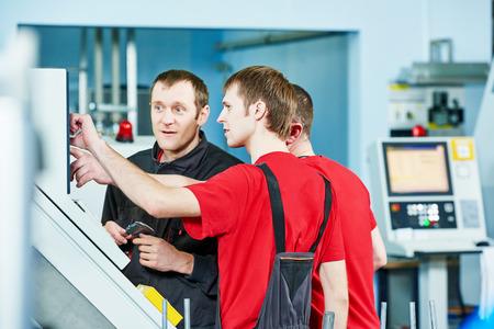 obrero trabajando: tres trabajadores de la industria de torneado CNC centro de la máquina en el taller de fabricación de herramientas Foto de archivo