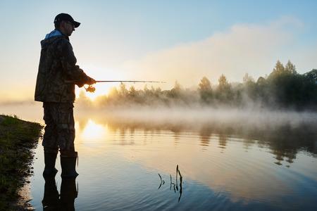 hombre pescando: Fisher hombre de la pesca con el giro varilla en una orilla del río en brumoso amanecer brumoso