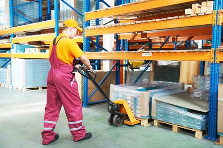 carretillas almacen: Trabajador de sexo masculino en el almacén de trabajo con la carretilla elevadora mano Foto de archivo