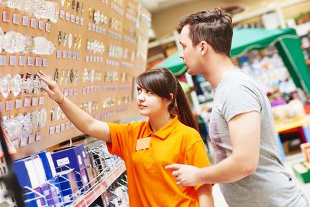 hardware: Asistente femenina joven vendedor ayuda a elegir la l�mpara comprador en el hardware centro comercial supermercado Foto de archivo