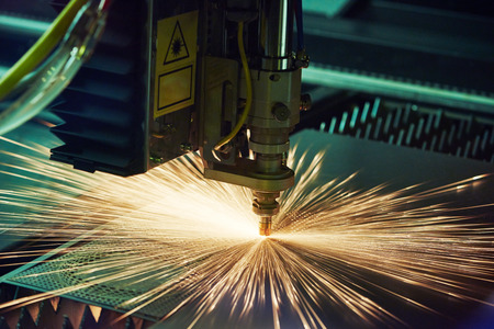precision: metal working. Laser cutting technology of flat sheet metal steel material processing with sparks. Authentic shooting in challenging conditions. Maybe little blurred.