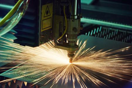 herramientas de mecánica: trabajo de los metales. La tecnología de corte por láser de chapa plana de procesamiento de material de acero de metal con las chispas. Tiroteo Auténtico en condiciones difíciles. Tal vez poco borrosa.