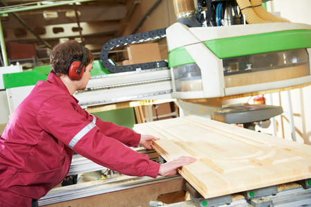 industrial carpenter worker operating wood cutting machine during wooden door furniture manufacturing Stockfoto