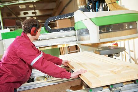 industrial carpenter worker operating wood cutting machine during wooden door furniture manufacturing Standard-Bild