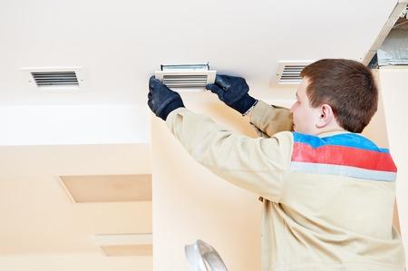 aire acondicionado: trabajador industrial instalación de ventilación o aire acondicionado soporte del filtro en el techo Foto de archivo