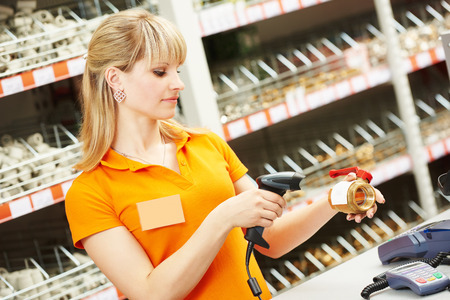 seller cashier with bar code scanner scanning plumber valve at store Stock Photo