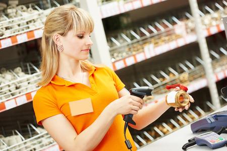 codigos de barra: vendedor cajera con válvula de fontanero de exploración escáner de código de barras en la tienda Foto de archivo