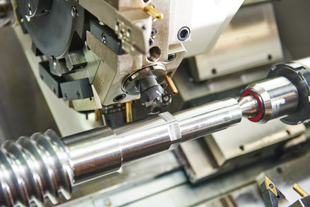 metalworking  industry: mill cutting tool ready to process steel metal shaft on lathe machine in workshop