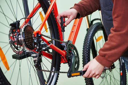 Bike service: mechanic serviceman repairman tuning and assembling or adjusting bicycle chain in workshop photo