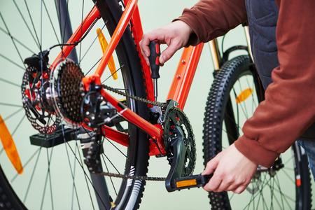 mecanico: Tuning reparador militar mecánico y montaje o ajuste de cadena de la bicicleta en el taller: el servicio de bicicletas Foto de archivo
