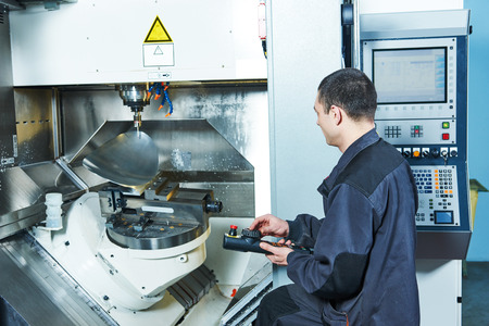 metalwork industry. worker operating cnc milling machine center in tool manufacture workshop 스톡 콘텐츠