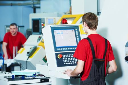 mecanica industrial: trabajador industrial mecánica en cnc centro fresadora en el taller de fabricación de herramientas