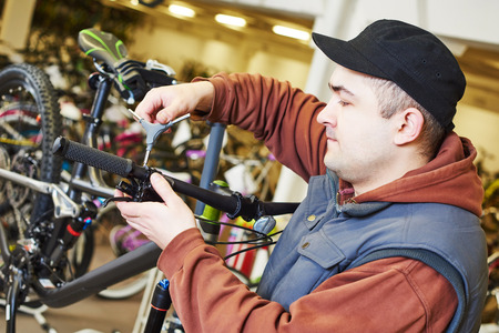 serviceman: Bike maintenance: mechanic serviceman repairman installing assembling or adjusting bicycle gear on wheel in workshop