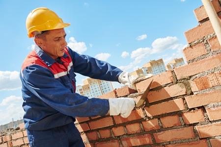 constructor: Obrero. albañil albañil instalación de ladrillo rojo con espátula llana aire libre