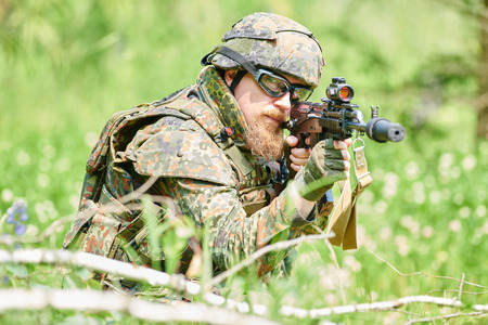 nato: military. soldier targeting  with assault rifle at position in nato germany uniform outdoors