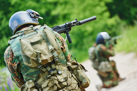 assault forces: military. two soldier with assault rifle in uniform patrolling territory outdoors