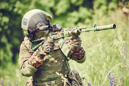 recon: military. soldier in uniform targeting with assault rifle outdoors