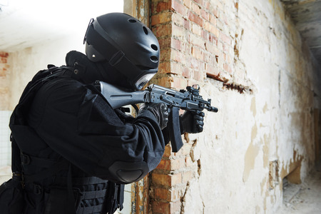 Military industry. Special forces or anti-terrorist police soldier,  private military contractor armed with assault rifle ready to attack during clean-up operation, mission photo