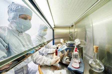 laboratory research: female science researchers in protective uniform and equipment works with dangerous hazard virus material at microbilogy laboratory