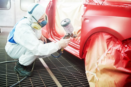 auto painting worker. red car in a paint chamber during repair work Stock Photo