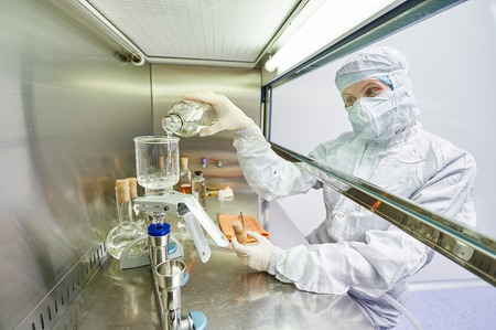 material: female science researchers in protective uniform and equipment works with dangerous hazard virus material at microbilogy laboratory