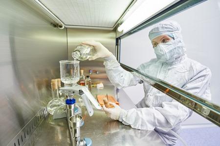 biologia: investigadores de ciencias de mujeres en uniforme y equipo de protección trabaja con material de virus en el laboratorio peligro peligroso Microbiología- Foto de archivo