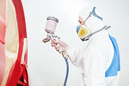 priming paint: auto painting worker. red car in a paint chamber during repair work Stock Photo