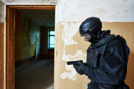 Military industry. Special forces or anti-terrorist police soldier,  private military contractor armed with pistol during clean-up operation, mission Stock Photo